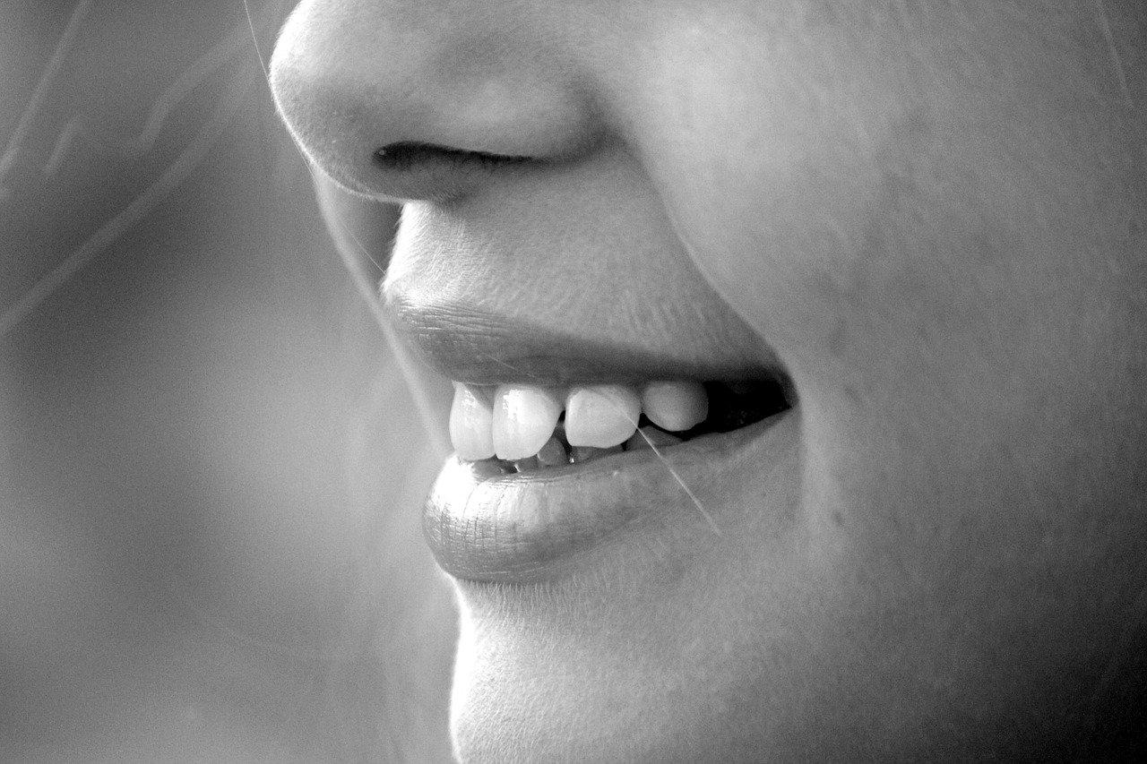 Gesicht, lächelnd und mit sichtbaren Zähnen